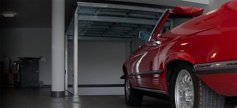 Hydraulic underground garage behind the red mercedes cabrio