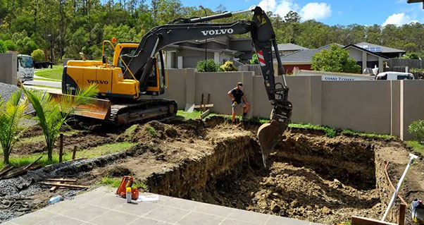 The excavator digs a pit for a hydraulic garage